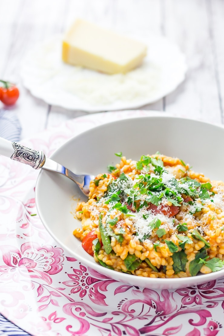 Cheesy pearl barley with tomatoes on a bowl with a fork and parmesan in the background