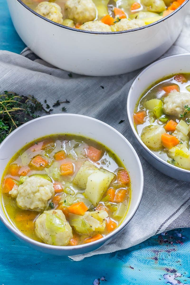 Two bowls of vegetable soup with dumplings with a pot of soup in the background