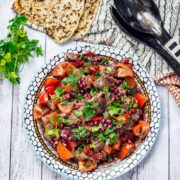 Overhead shot of Smoky Aubergine Salad with Red Pepper on a white wooden background with bread and parsley