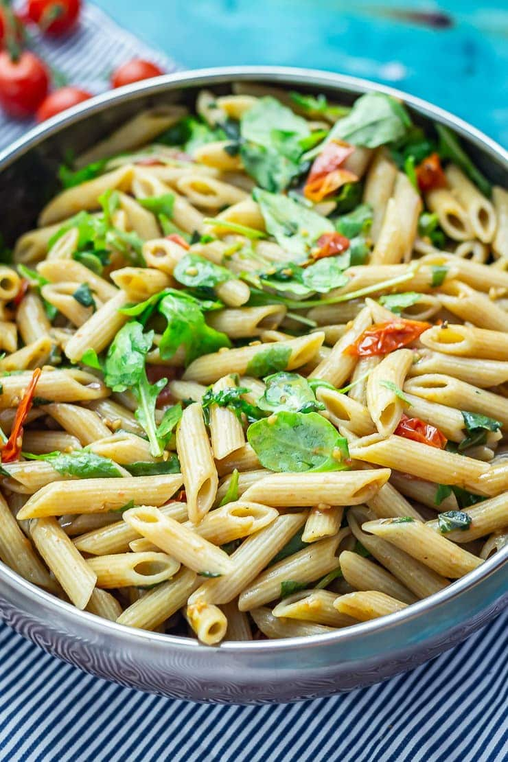 Close up of a big bowl of balsamic pasta salad on a blue background