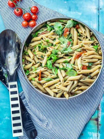 Overhead shot of Simple Pasta Salad with Balsamic on a striped cloth with salad servers and cherry tomatoes