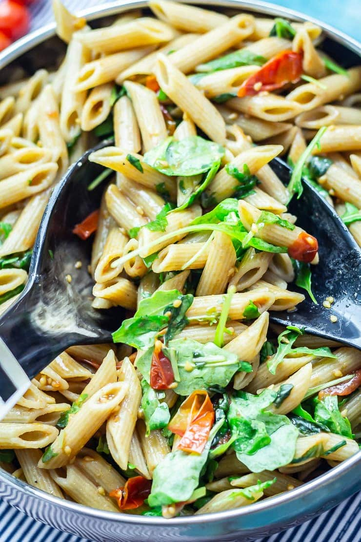 Close up of balsamic pasta salad with salad servers