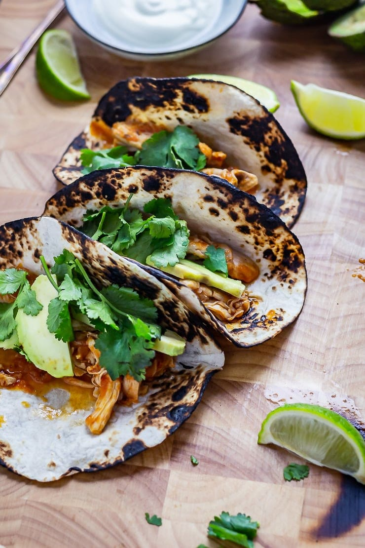 Chipotle chicken tacos on a wooden board with lime wedges