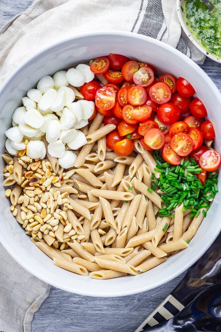 Overhead shot of caprese pasta salad with a cloth on a blue background