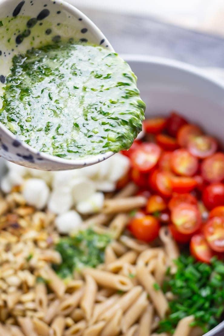 Basil dressing pouring onto caprese pasta salad