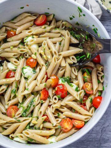 Overhead shot of caprese pasta salad with salad servers