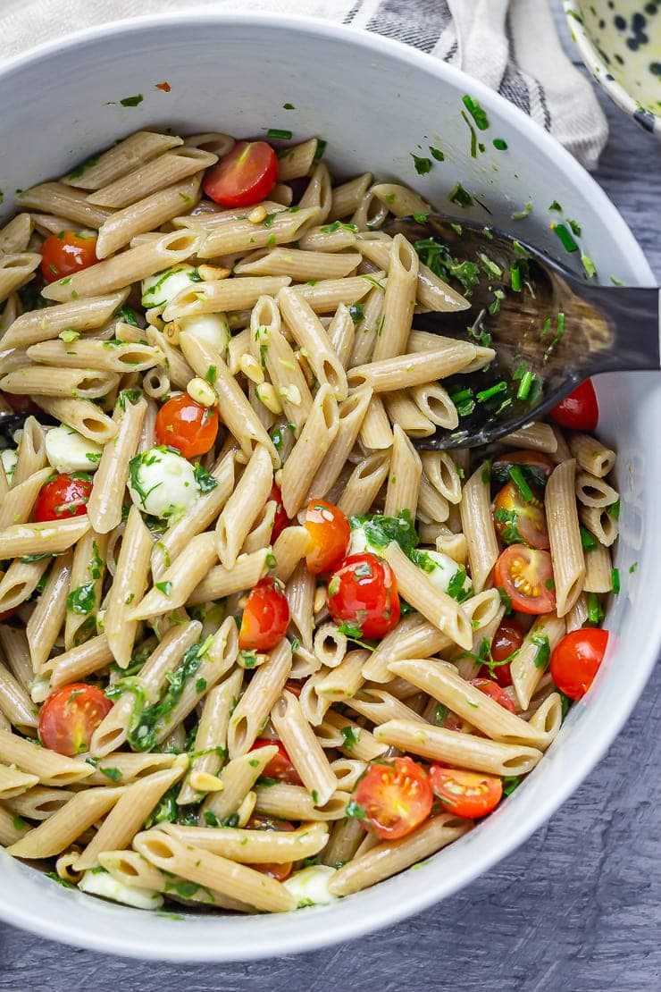 20 Minute Dinners: Overhead shot of caprese pasta salad with salad servers