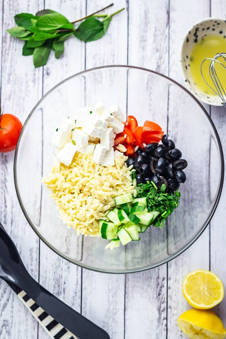 Overhead shot of Greek Orzo Salad with Lemon Dressing with lemon and mint on a white wooden background