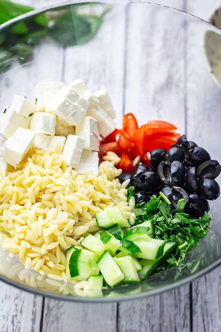 Ingredients for Greek orzo salad in a glass bowl on a white wooden background