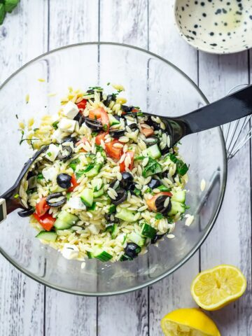 Overhead shot of Greek Orzo Salad with Herby Dressing on a white wooden background