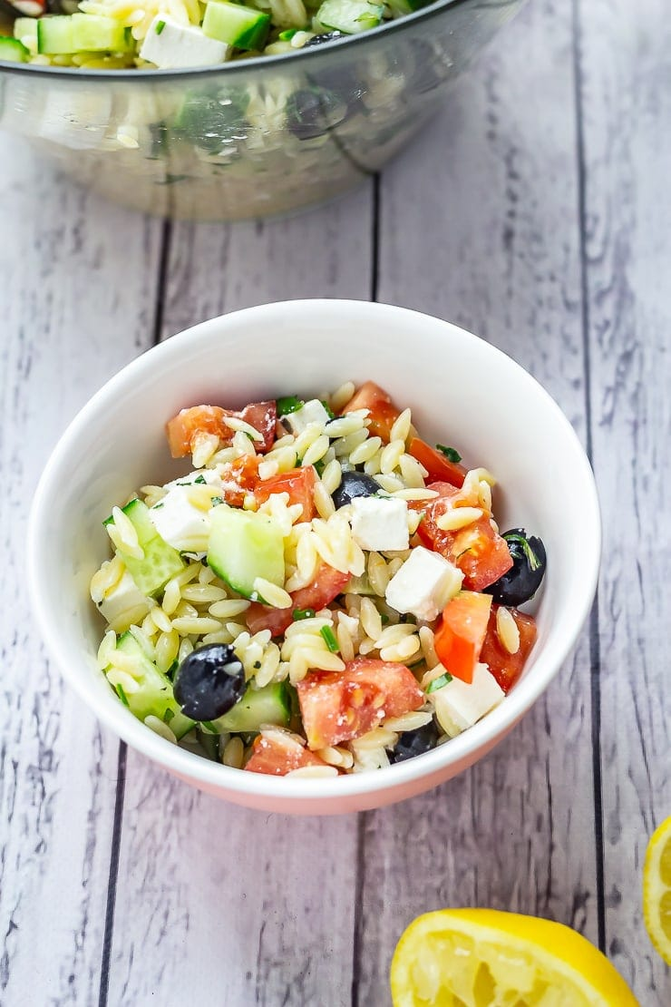 Small bowl of Greek Orzo Salad with Lemon Dressing on a white wooden background