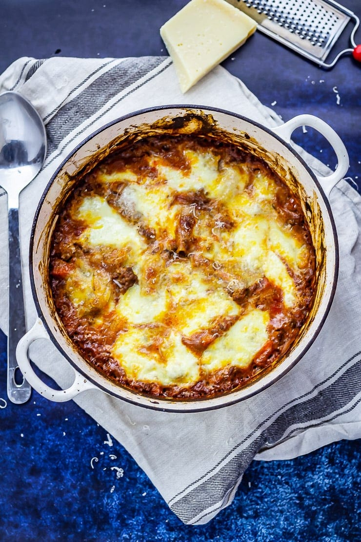Overhead shot of one pot lasagne on a blue background