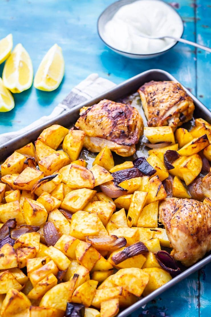 Sheet Pan Harissa Chicken with Potatoes on a blue background with lemon and yoghurt
