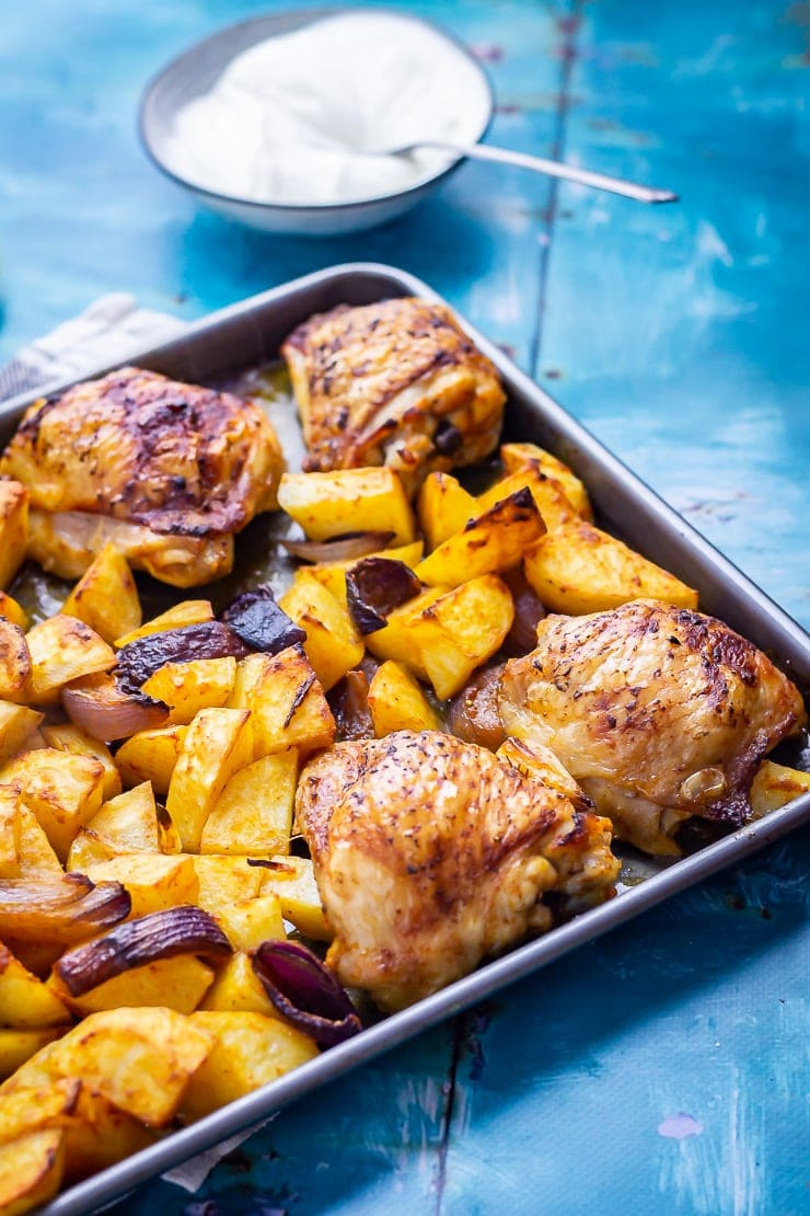 Sheet Pan Harissa Chicken with Potatoes on a blue background with garlic yoghurt
