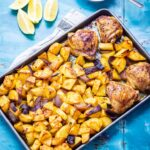 Overhead shot of sheet pan harissa chicken on a blue background with lemon and yoghurt