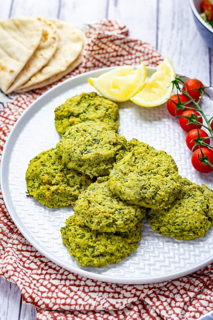 Platter of baked falafel with cherry tomatoes, lemon slices and flatbreads