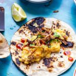 Breakfast tacos on a blue background with lime