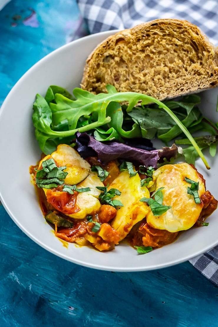 Bowl of tomato and halloumi bake with salad and bread on a blue background