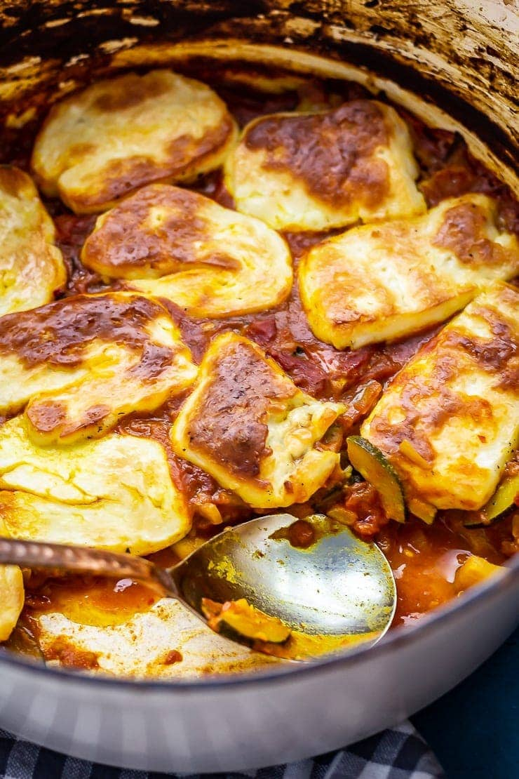 Tomato and halloumi bake with a portion taken and a spoon