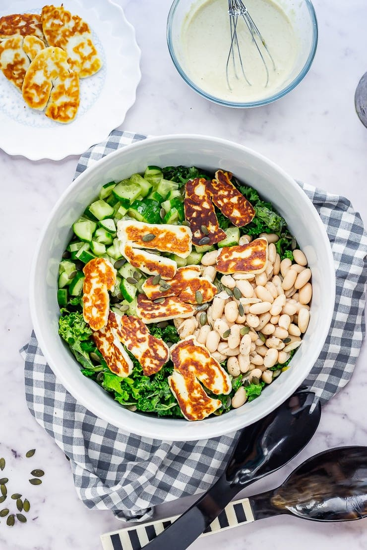 Overhead shot of halloumi salad with kale on a checked cloth on a marble background