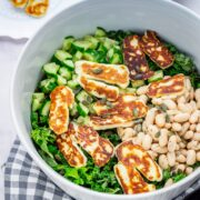 Halloumi salad in a bowl on a checked cloth on a marble background