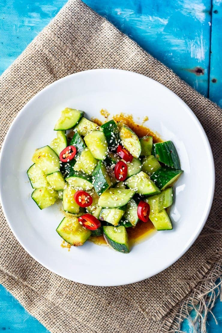 Overhead shot of sesame cucumber salad on a hessian background