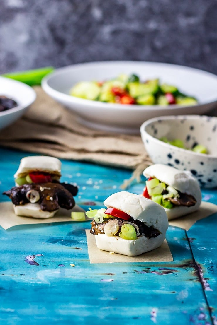 Photo of mushroom bao with cucumber salad in the background