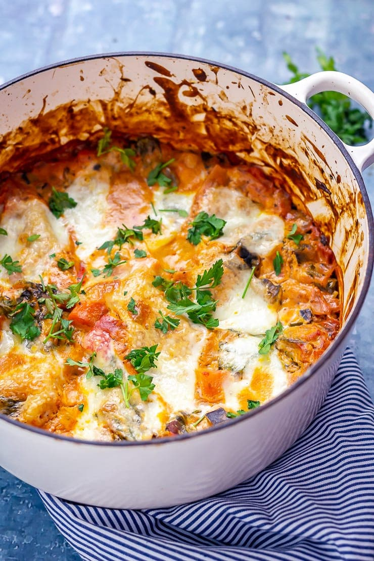 One pot vegetarian lasagne in a white pot on a striped cloth