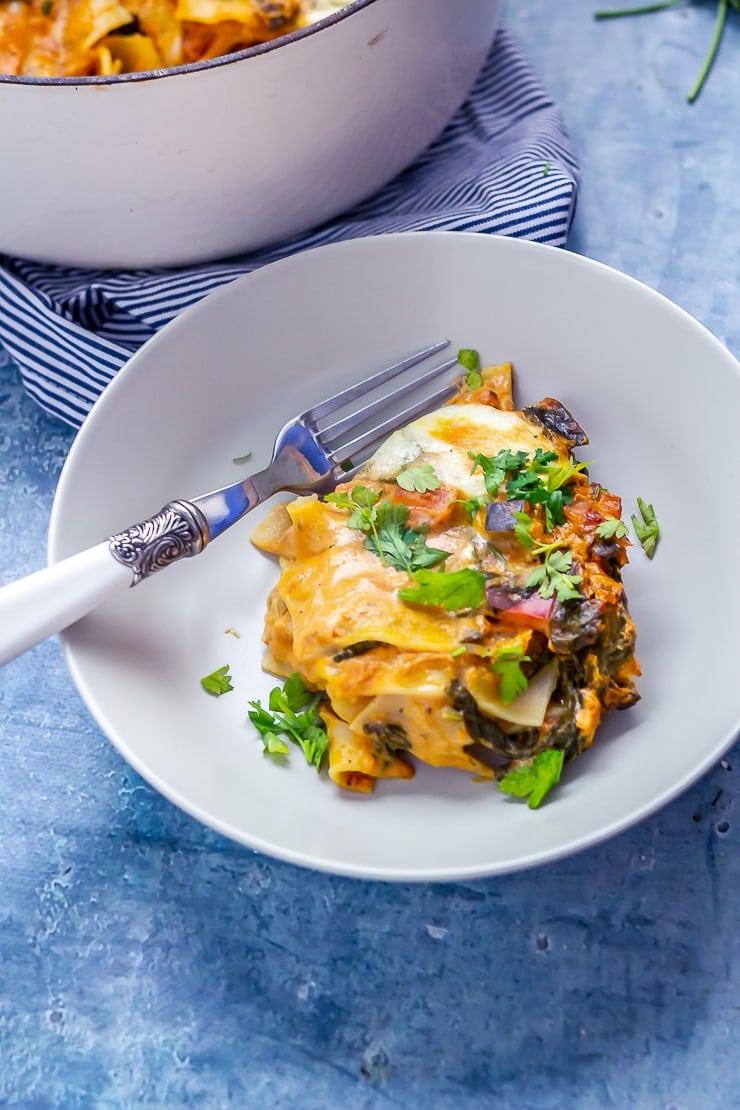 Portion of one pot vegetarian lasagne on a blue background