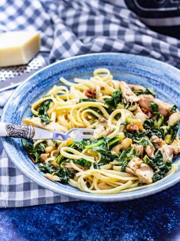 Bowl of pressure cooker chicken casserole stirred through pasta on a blue background