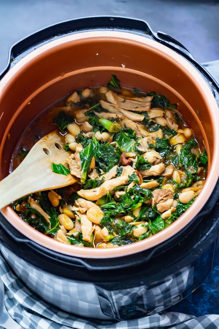 Chicken casserole in the pressure cooker with a wooden spatula