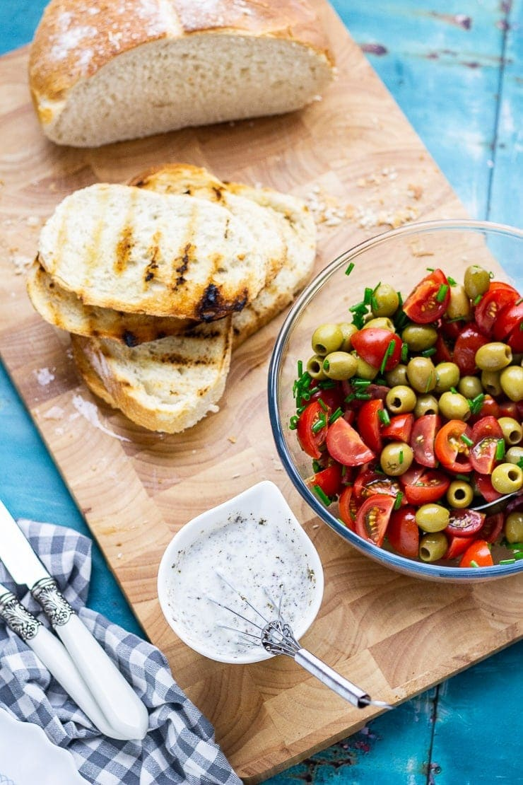 Overhead shot of tomato and olives in a bowl with toast and dressing on a wooden board over a blue background