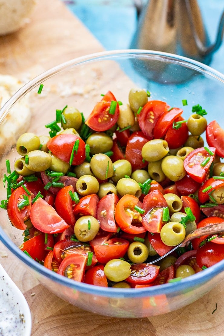 Bowl of olives and tomatoes on a wooden board