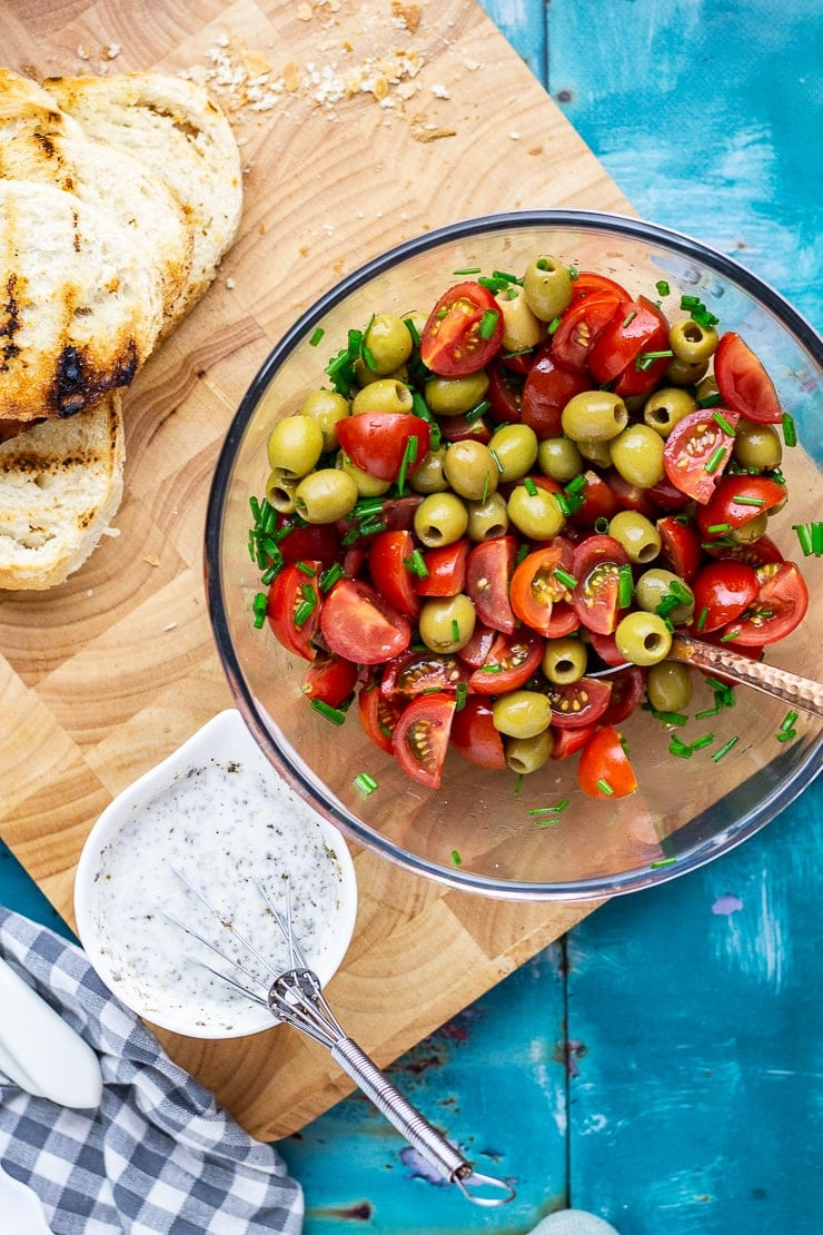 Bowl of olives and tomatoes on a wooden board with dressing and bread on a blue background