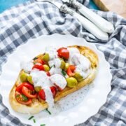 Olive and tomatoes on toast on a white plate on a checked cloth