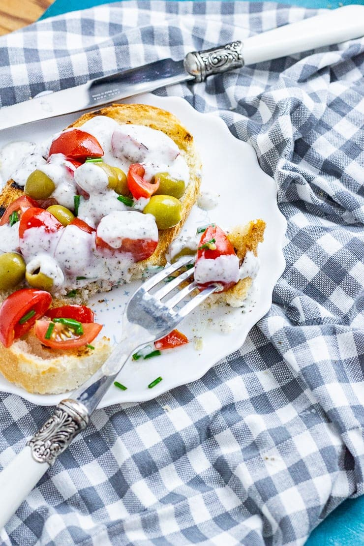 Olives and tomatoes on toast with dressing on a plate with a fork on a checked cloth