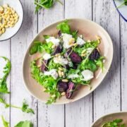 Overhead shot of beetroot salad on a white wooden background with rocket leaves