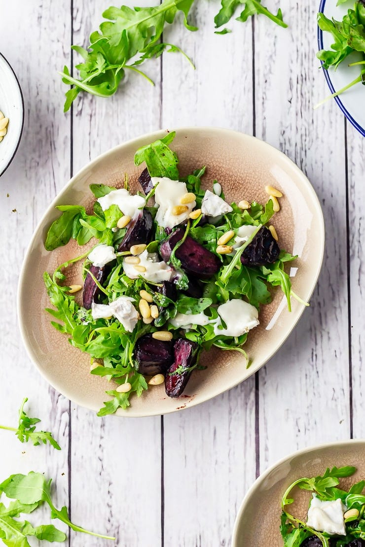 Overhead shot of beetroot salad with goat's cheese on a white wooden background