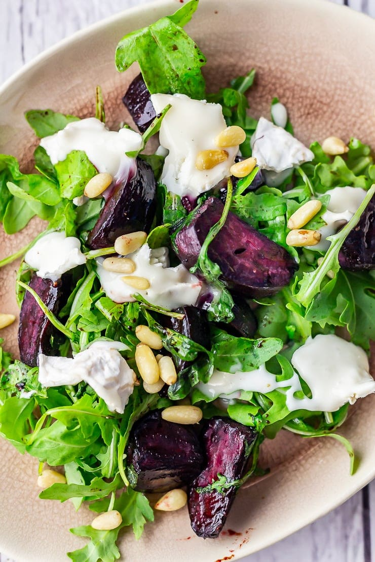 Overhead close up of beetroot salad with goat's cheese on a pink plate