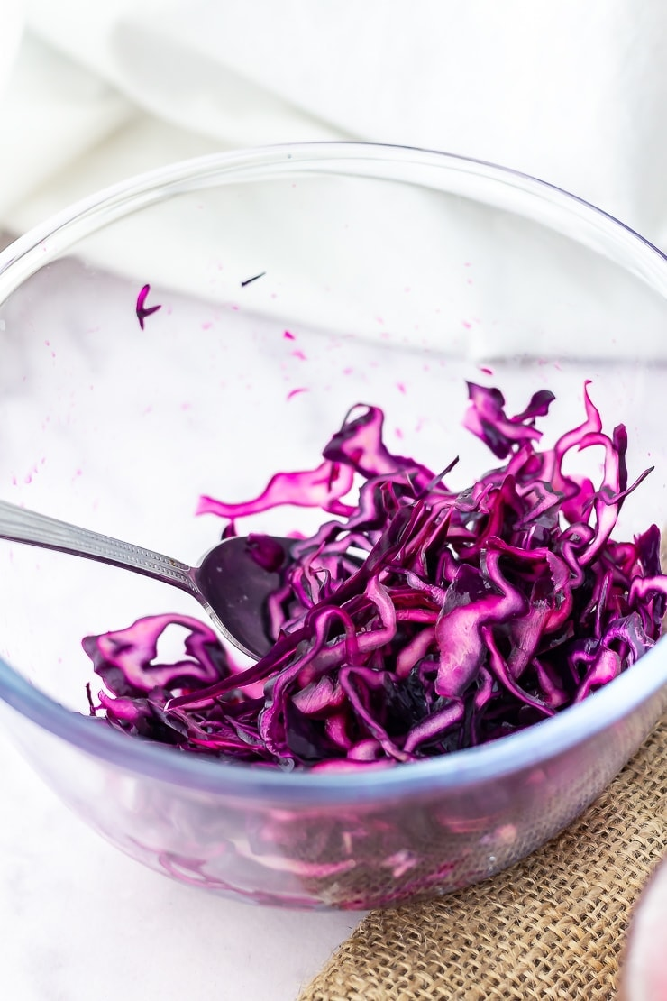 Red cabbage in a glass bowl on a marble background