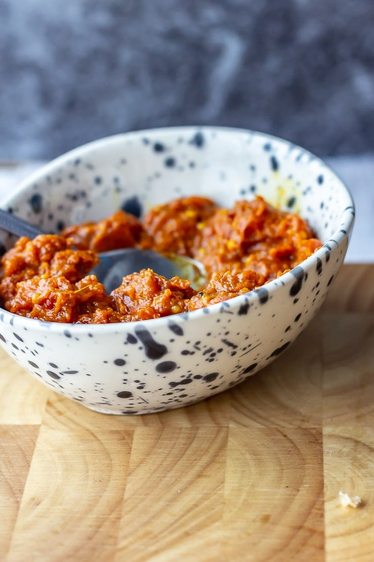 Bowl of harissa to go with veggie burgers on a wooden board