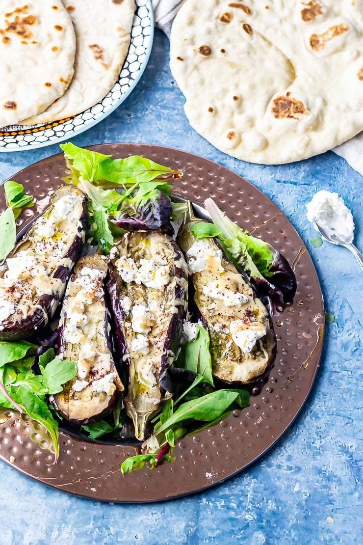 Overhead shot of baked aubergine with tahini on a platter with flatbread on a blue background