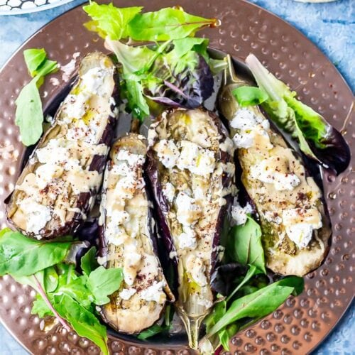 Overhead shot of baked aubergine with tahini and goat's cheese with lettuce leaves on a blue background