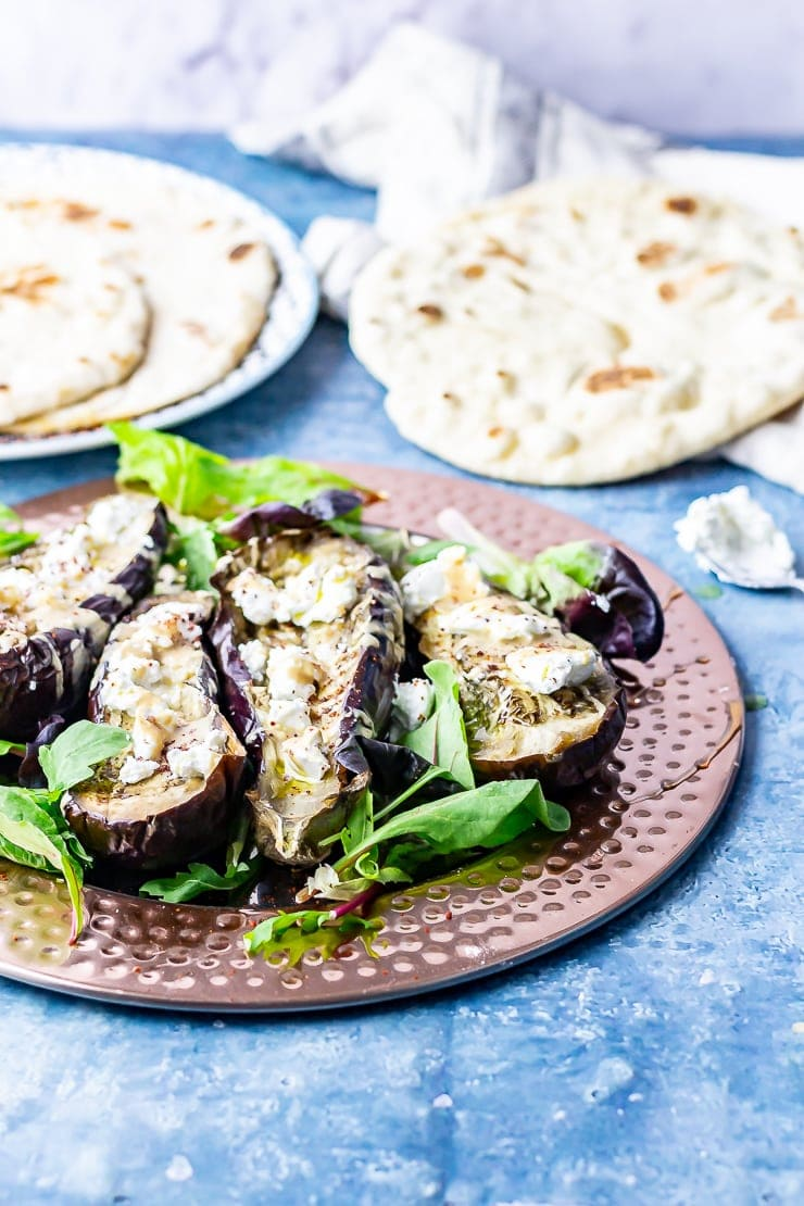Side on shot of baked aubergine with tahini and goat's cheese on a blue background