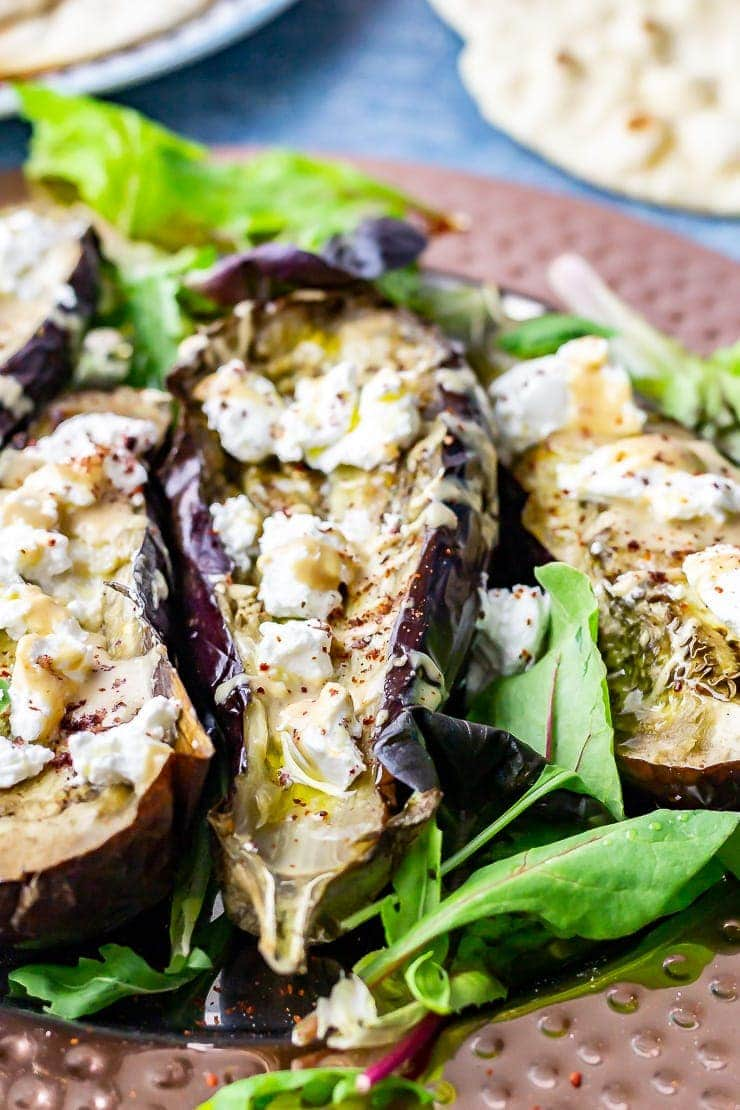 Close up of baked aubergine with goat's cheese on a platter with salad leaves