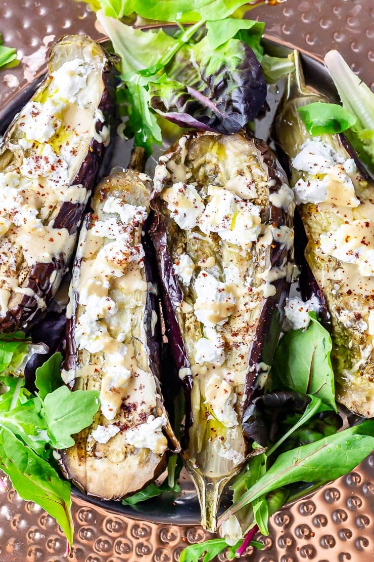 Close up shot of baked aubergine with tahini and goat's cheese with salad leaves on a platter