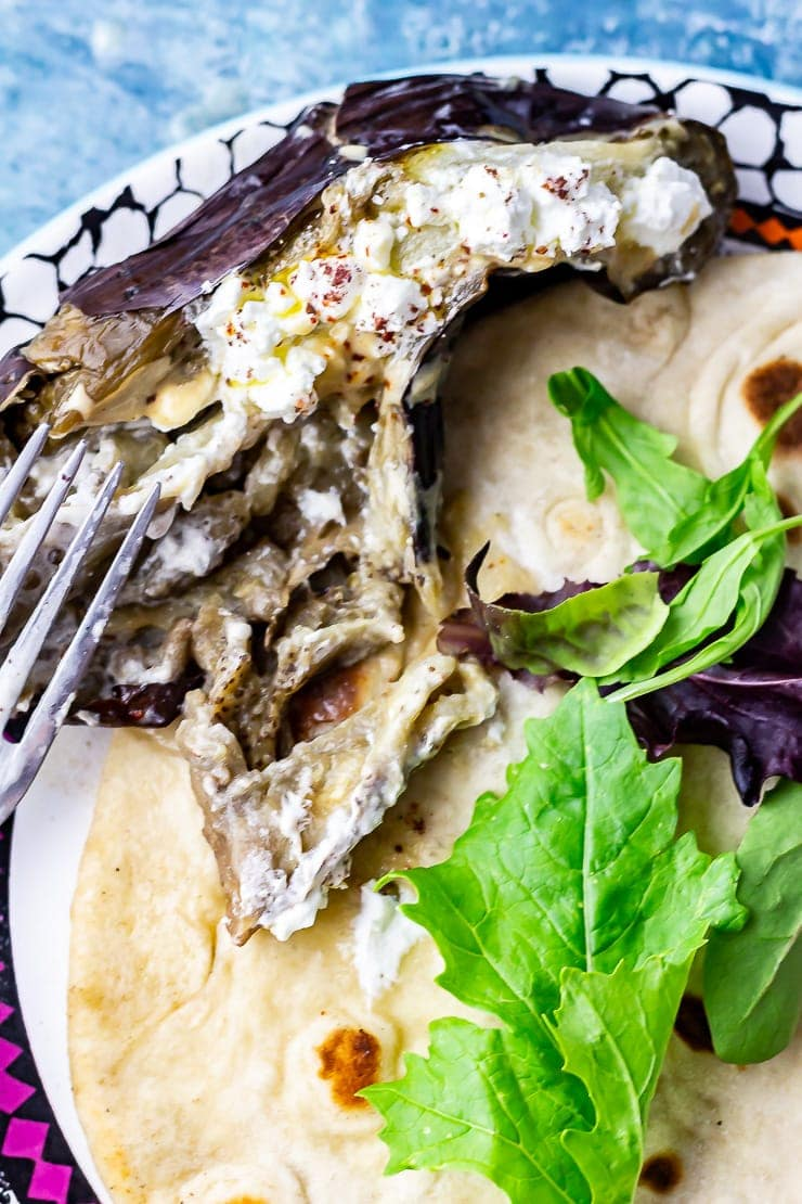 Baked aubergine with a fork on a plate with flatbread