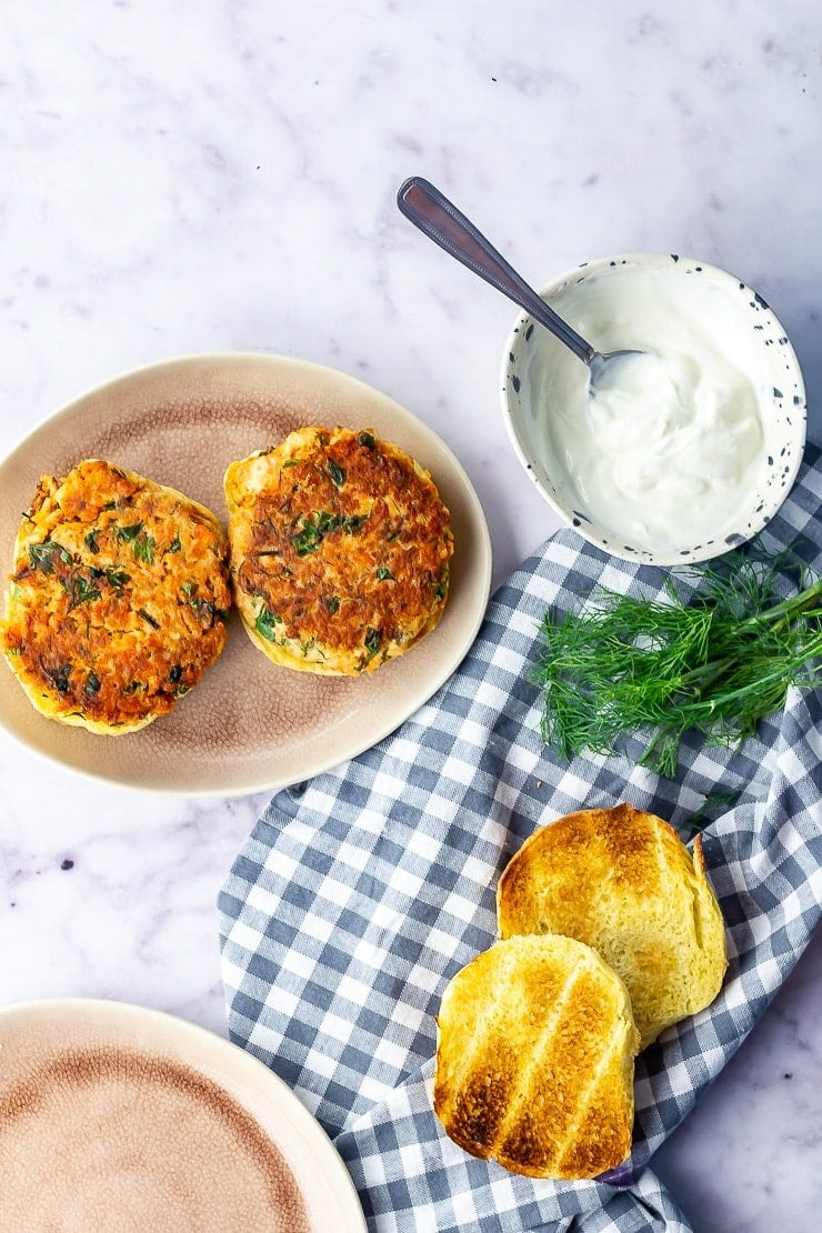 Overhead shot of salmon burgers with toasted brioche on a checked cloth over a marble background