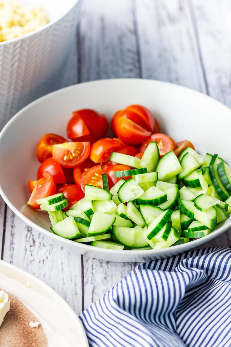 Bowl of sliced cucumber and tomato for summer salad on a white wooden background