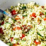 Summer salad with pearl barley in a bowl with a spoon